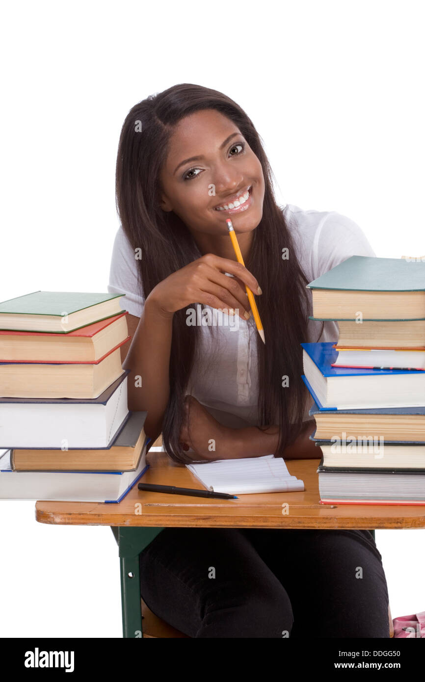 High School Or College Ethnic African American Female Student Sitting By Desk With Lot Of Books In Class Library Doing Homework