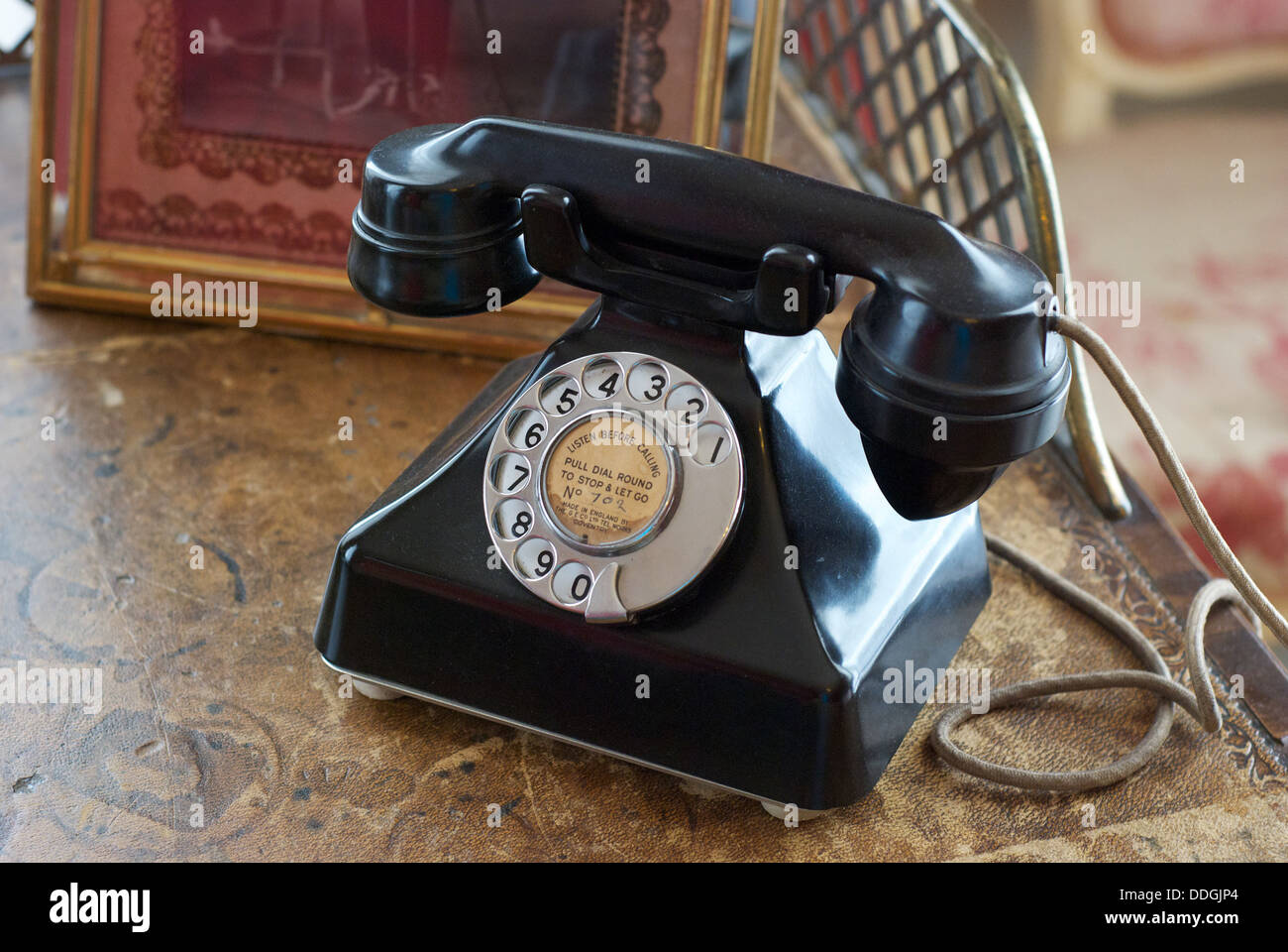 Retro vintage old bakelite telephone on a side table in a british country house - Stock Image
