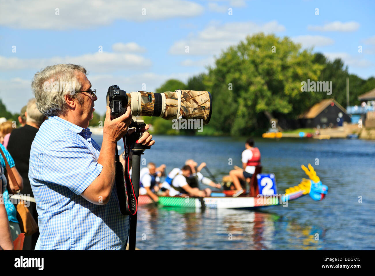 Professional photographer with a Canon camera and a big telephoto lens on a monopod - Stock Image