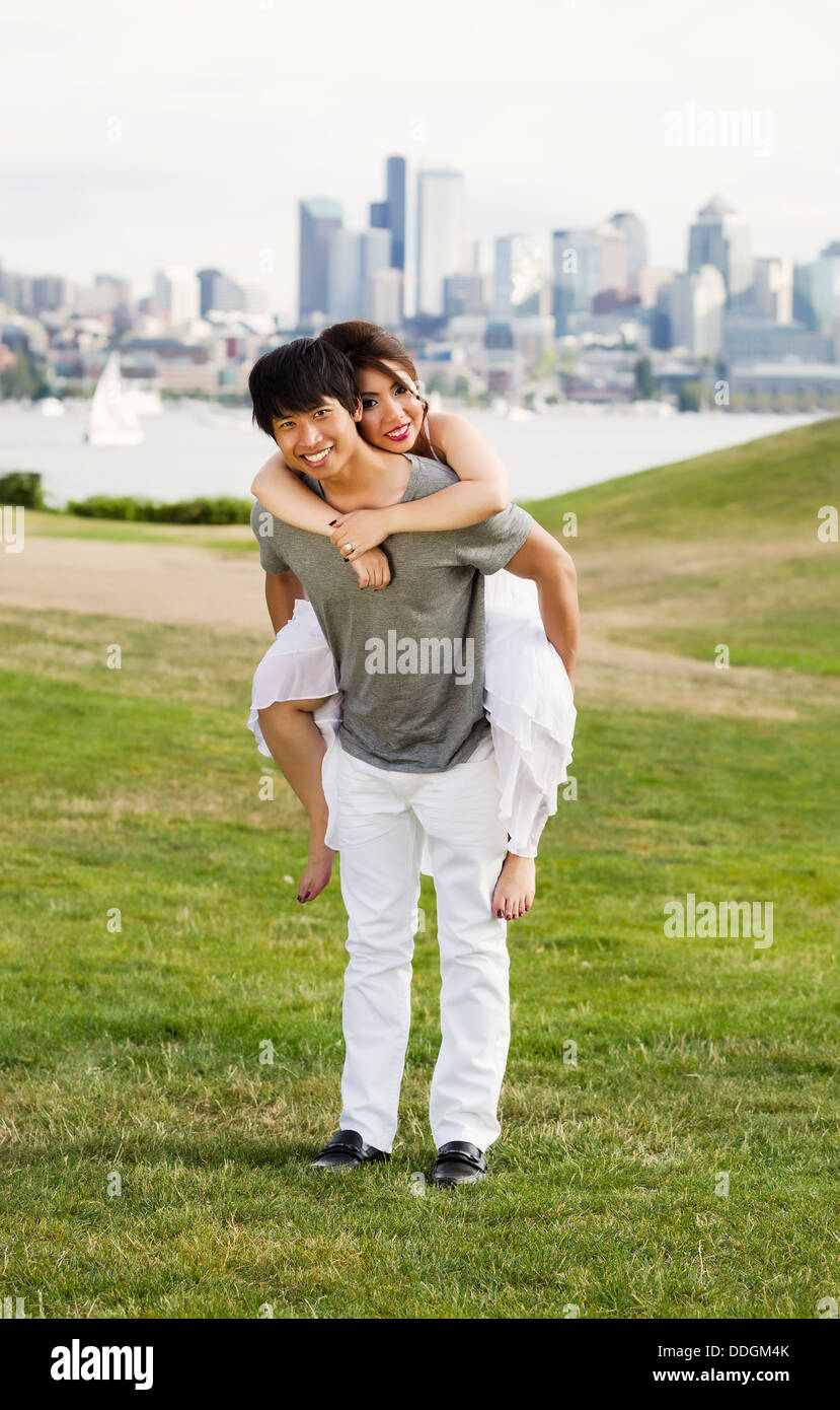 Vertical photo of young adult couple, facing forward, woman on back of man with city of Seattle and harbor in Background - Stock Image