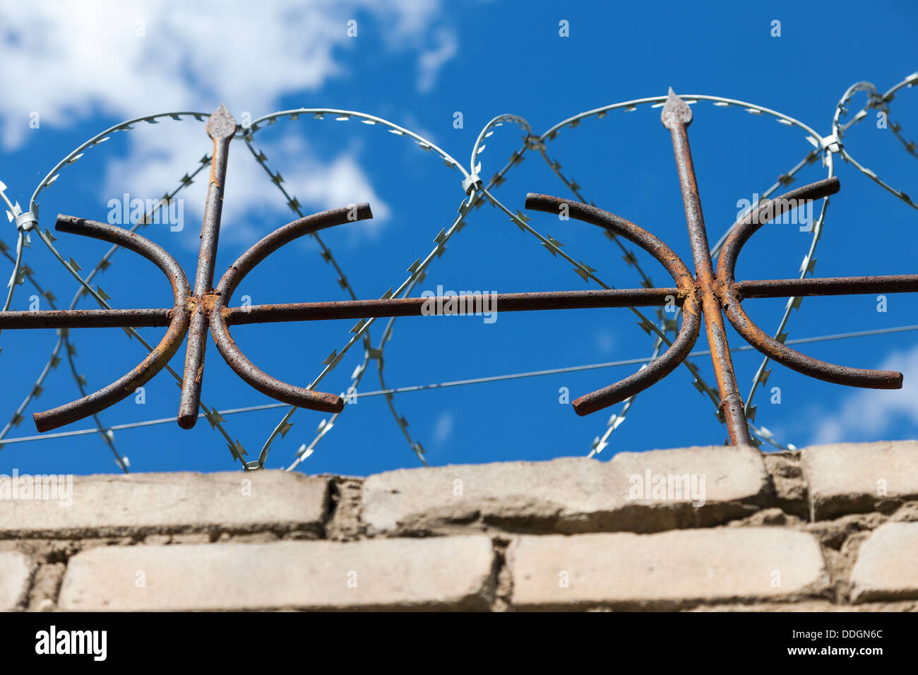 Barbed wire on the fence against a bright blue sky - Stock Image