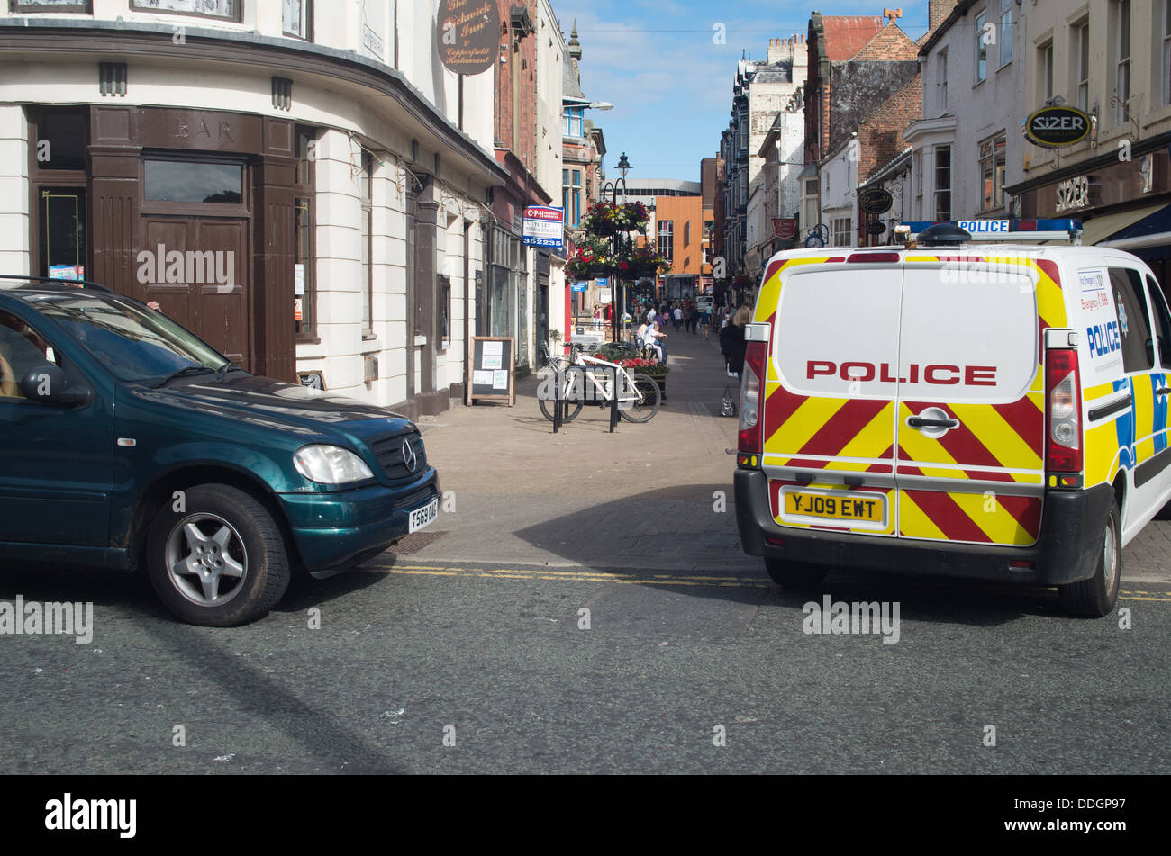 Police car drives past illegally parked 4X4 - Stock Image