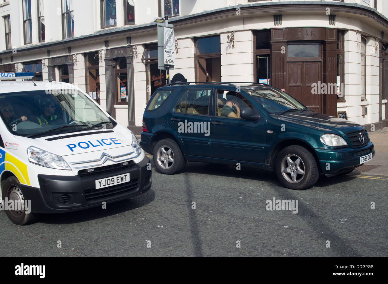 Police van drives past illegally parked 4X4 on double yellow lines - Stock Image