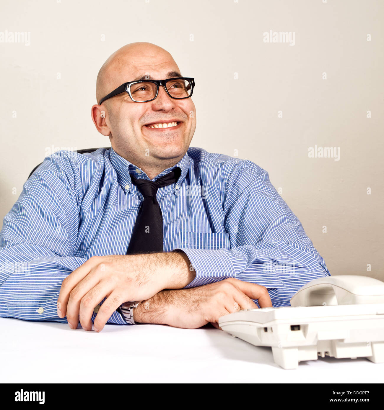 Smiling businessman at office desk with telephone. Wheeler dealer or business crook. - Stock Image