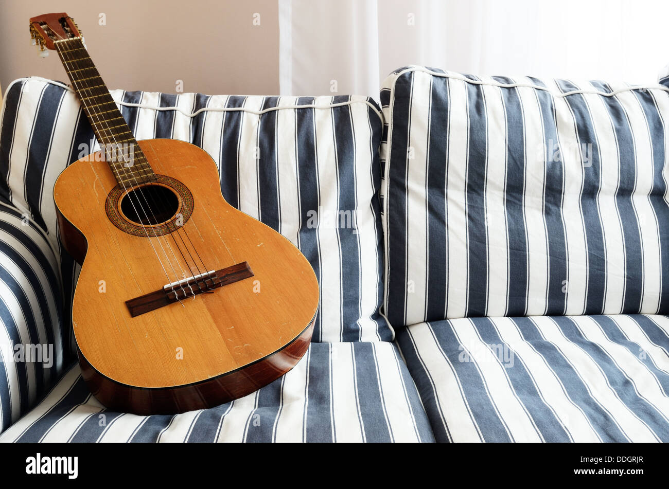 acoustic guitar on a striped couch, horizontal - Stock Image