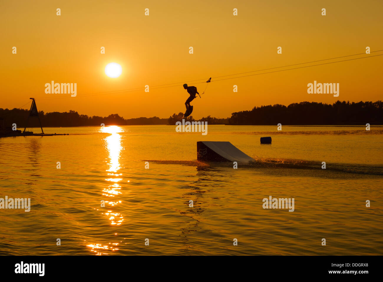 Silhouette of a man cable wakeboarding - Stock Image