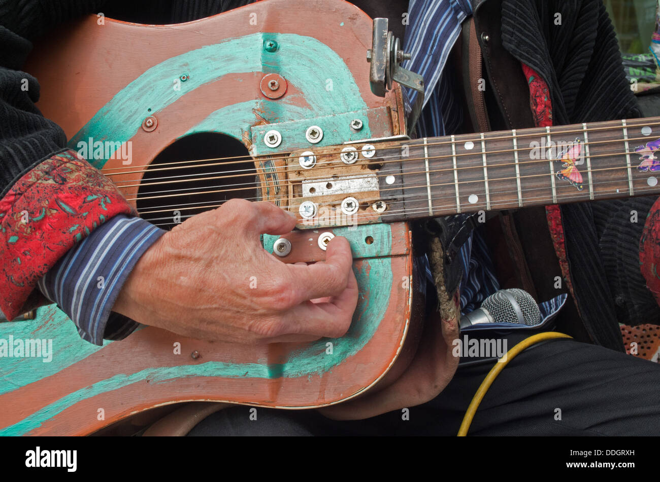 Man playing a repaired hand painted guitar Stock Photo
