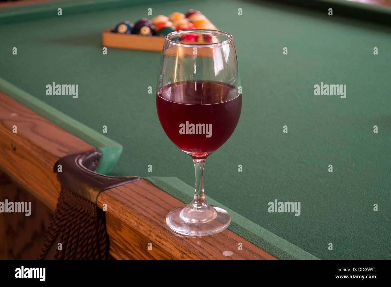 red wine in a single clear glass on a pool table with a rack of pool balls in the background sitting on an oak table - Stock Image
