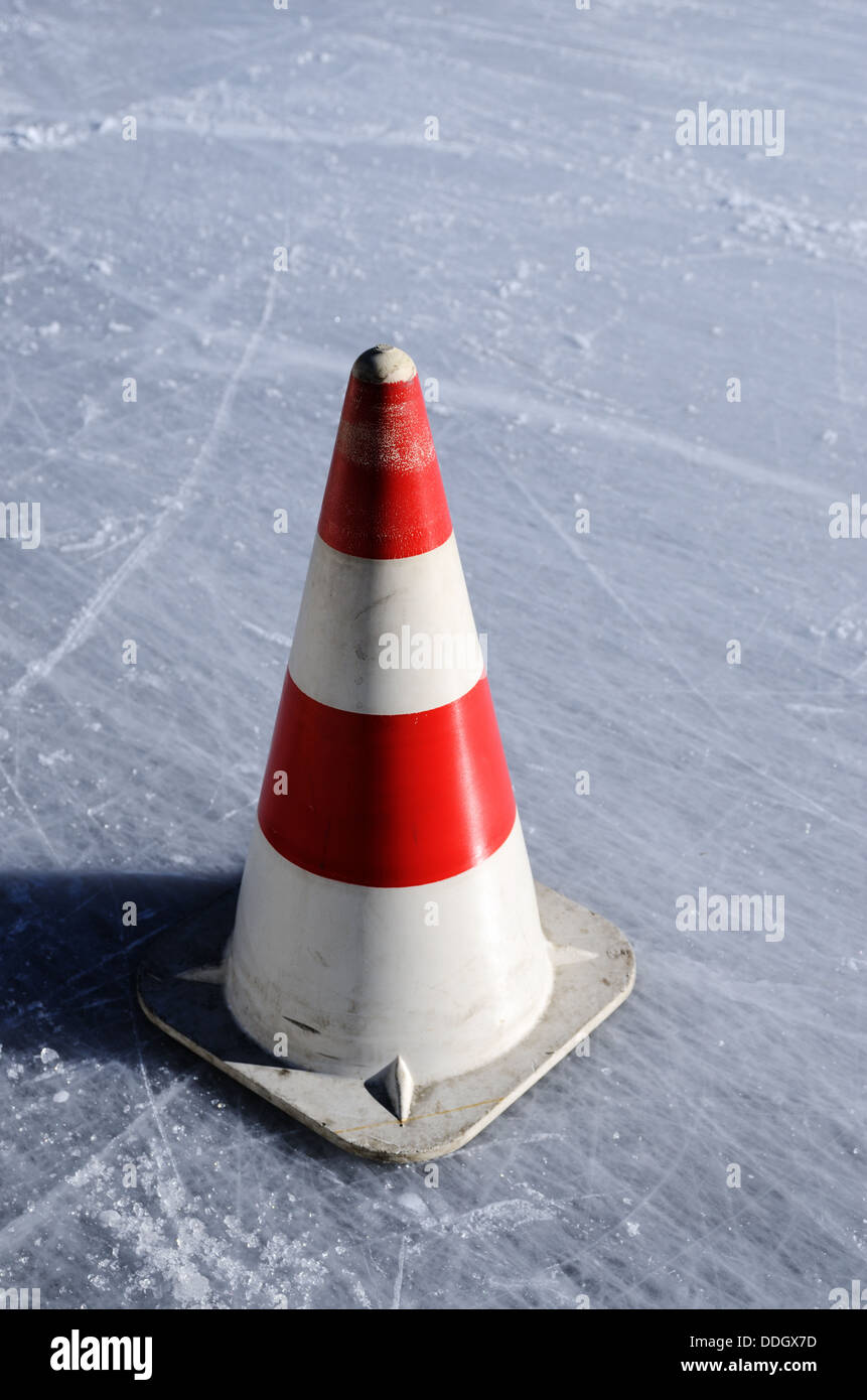 red white striped cones on the ice rink, vertical - Stock Image