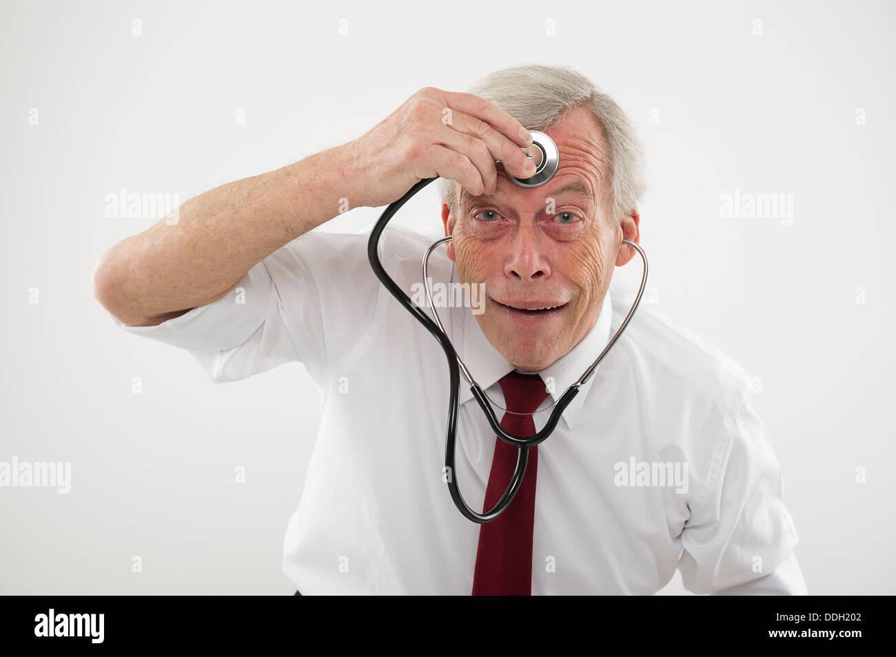 Senior man holding a stethosope to his forehead - Stock Image