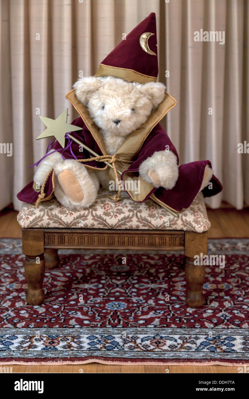 Creamy white stuffed teddy bear wearing burgundy and gold trimmed magician's coat and pointed hat holding a gold star magic wand - Stock Image