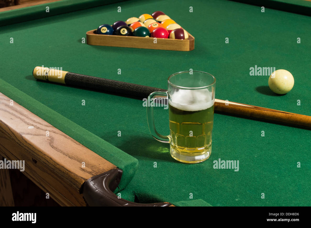 A Cold Mug Of Beer With Foam On A Pool Table With Green Felt, A Pool Stick  And Rack Of 15 Balls Including 8 Ball And 9 Ball.