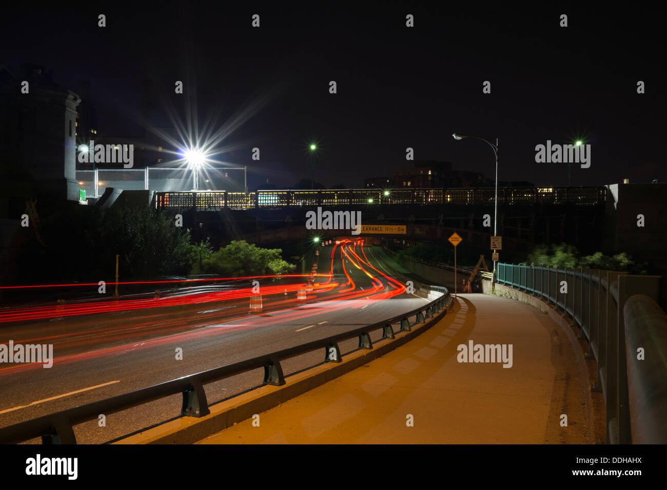 Deserted sidewalk and blurred car lights going under bridge along Memorial Drive - Stock Image