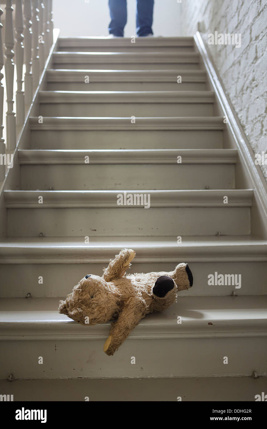 Teddybear on steps while man in background - Stock Image