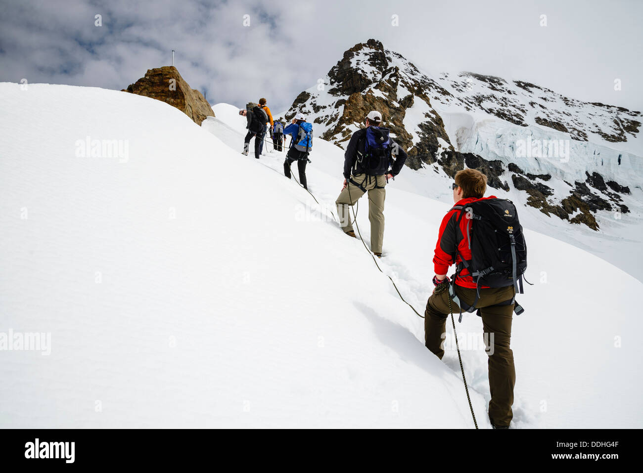 Climbers on the ridge of the Jungfraujoch, near Grindelwald Switzerland, with the south-west ridge of the Monch Stock Photo