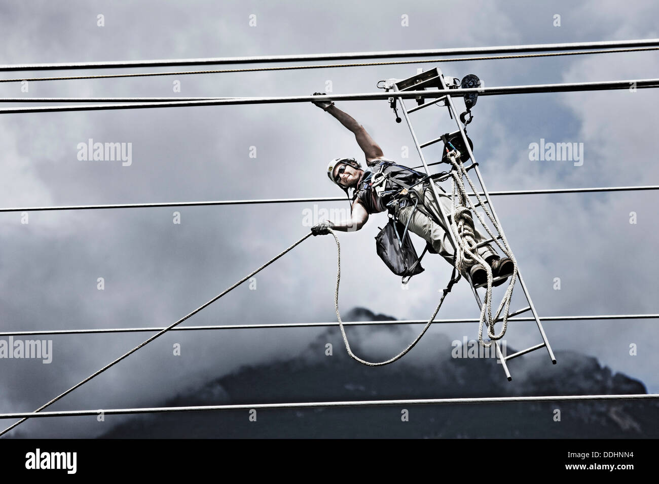 High-voltage service technician pulling a rope to get to the next ...