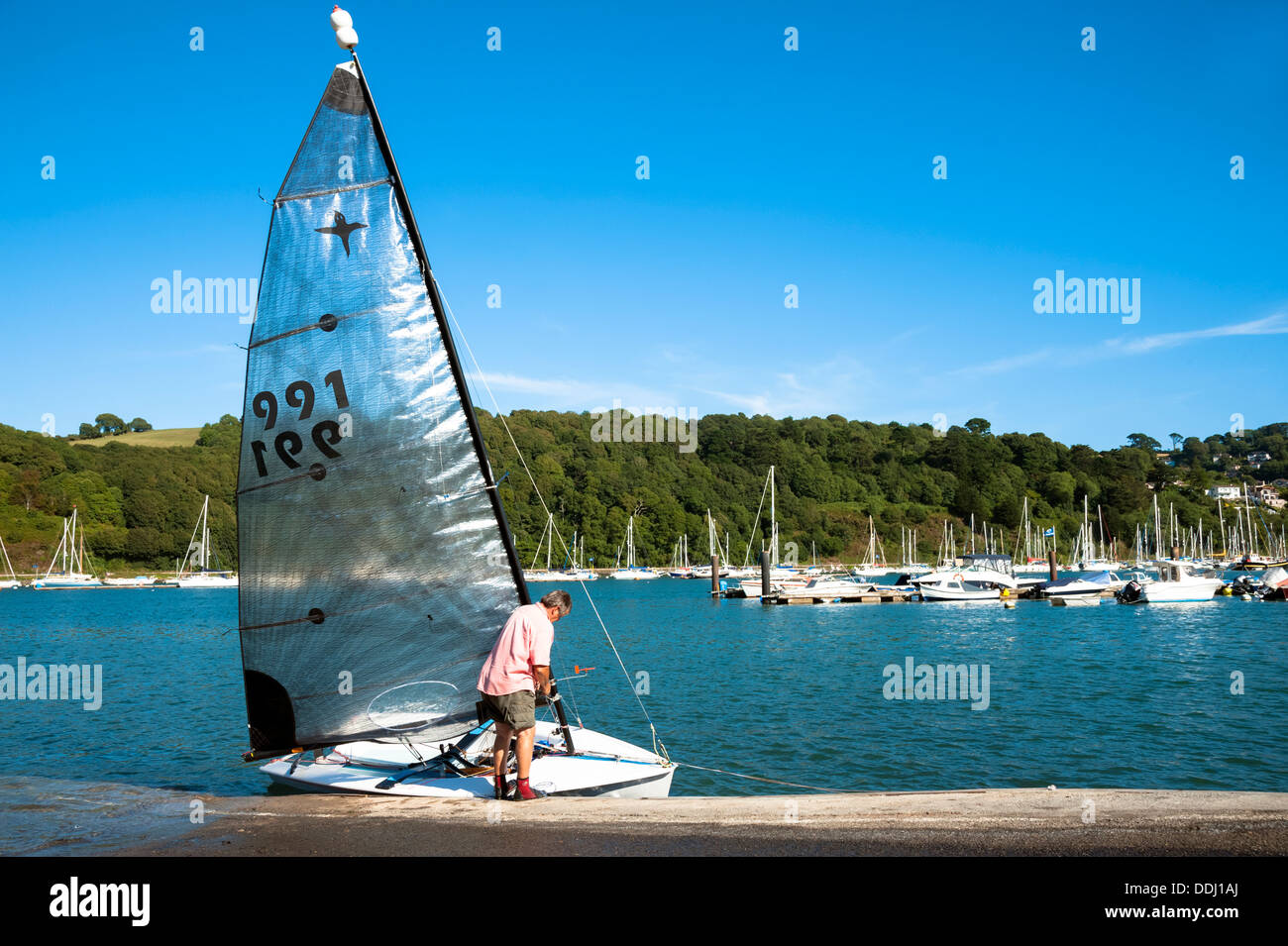 Man getting a sailing dinghy ready for a trip on the river at Dartmouth, Devon, UK. - Stock Image