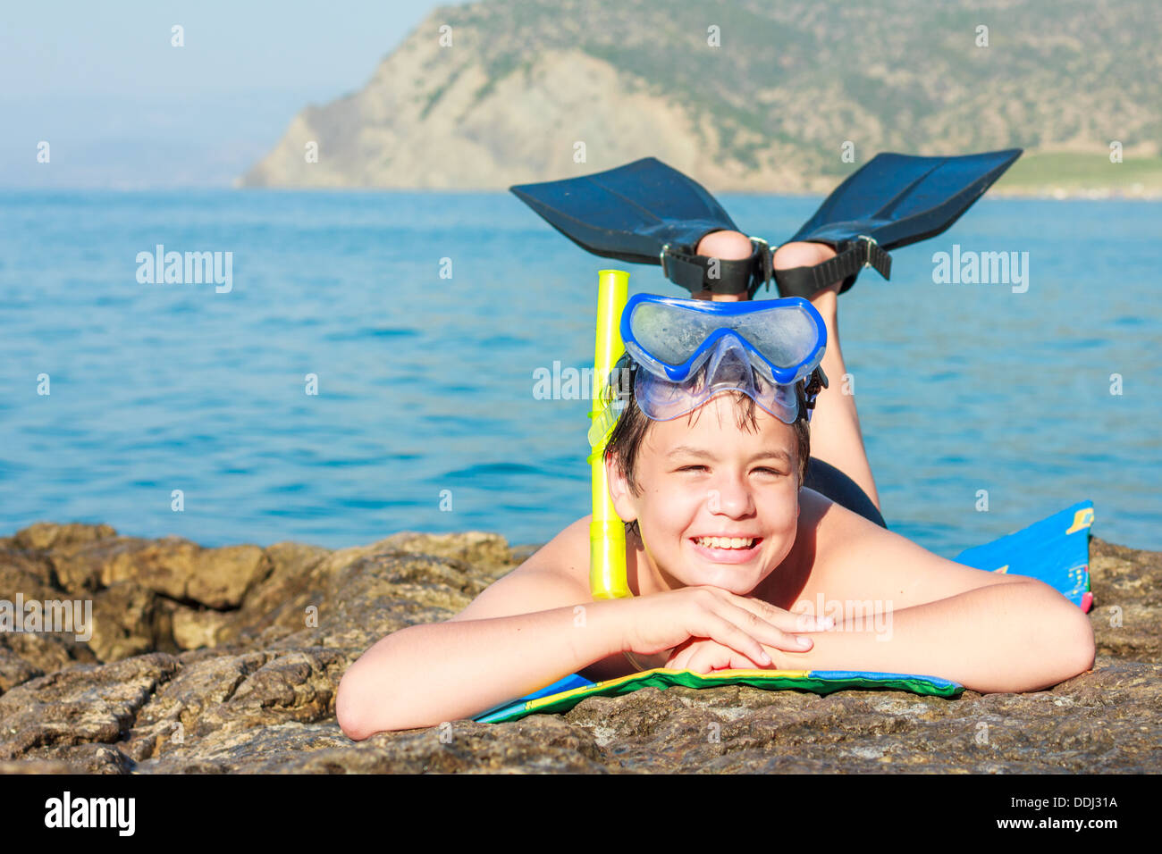 close-up portrait of a happy laughing boy of twelve in a mask and fins on the sea beach - Stock Image