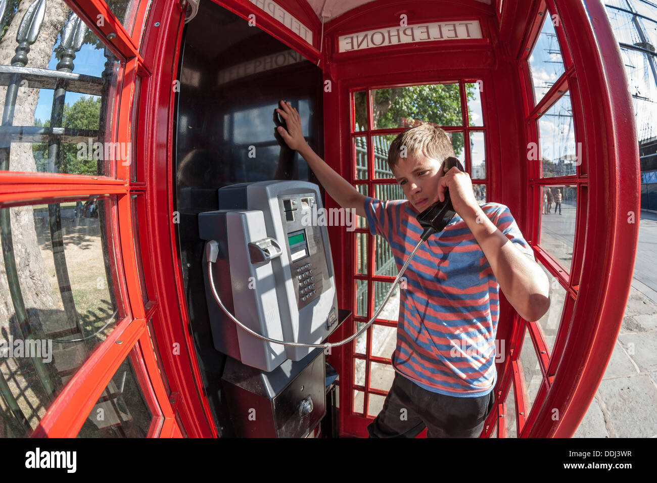 Teenager using phone in red telephone box - Stock Image