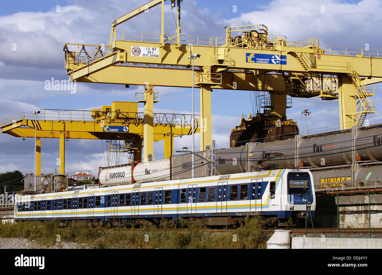 Euskotren with bridge cranes in background. Cross-border freight train station. Irun. Guipuzcoa. Basque Country. Spain - Stock Image