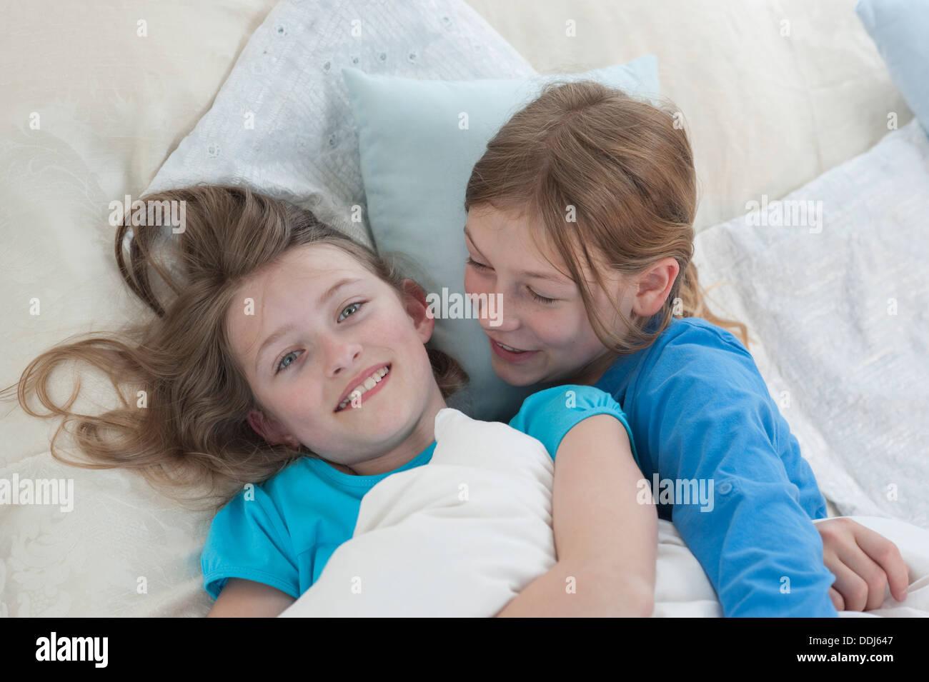 Germany, Bavaria, Girls telling secrets on bed, smiling - Stock Image