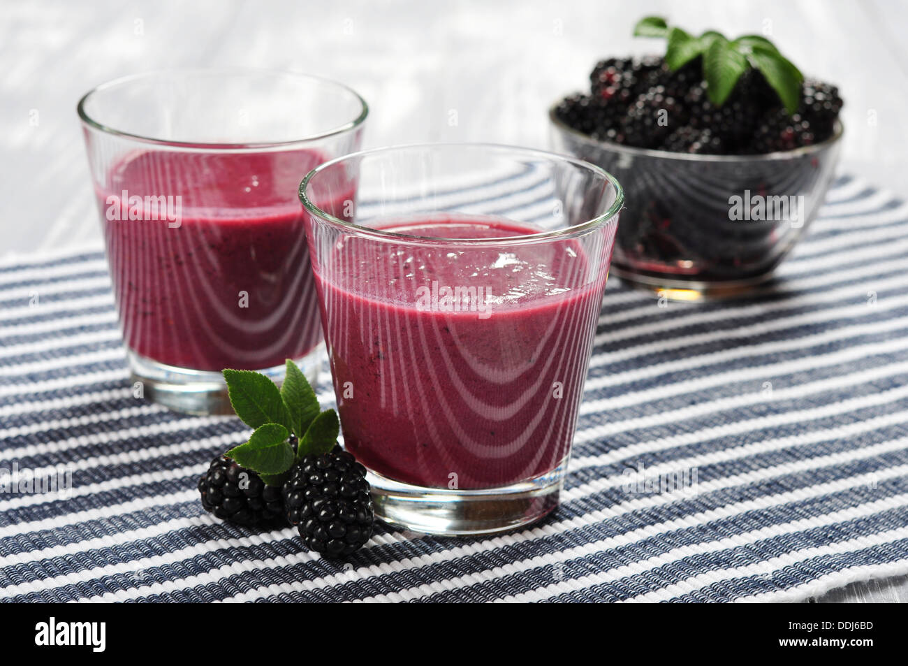 Blackberry smoothie with fresh blackberries on wooden background - Stock Image
