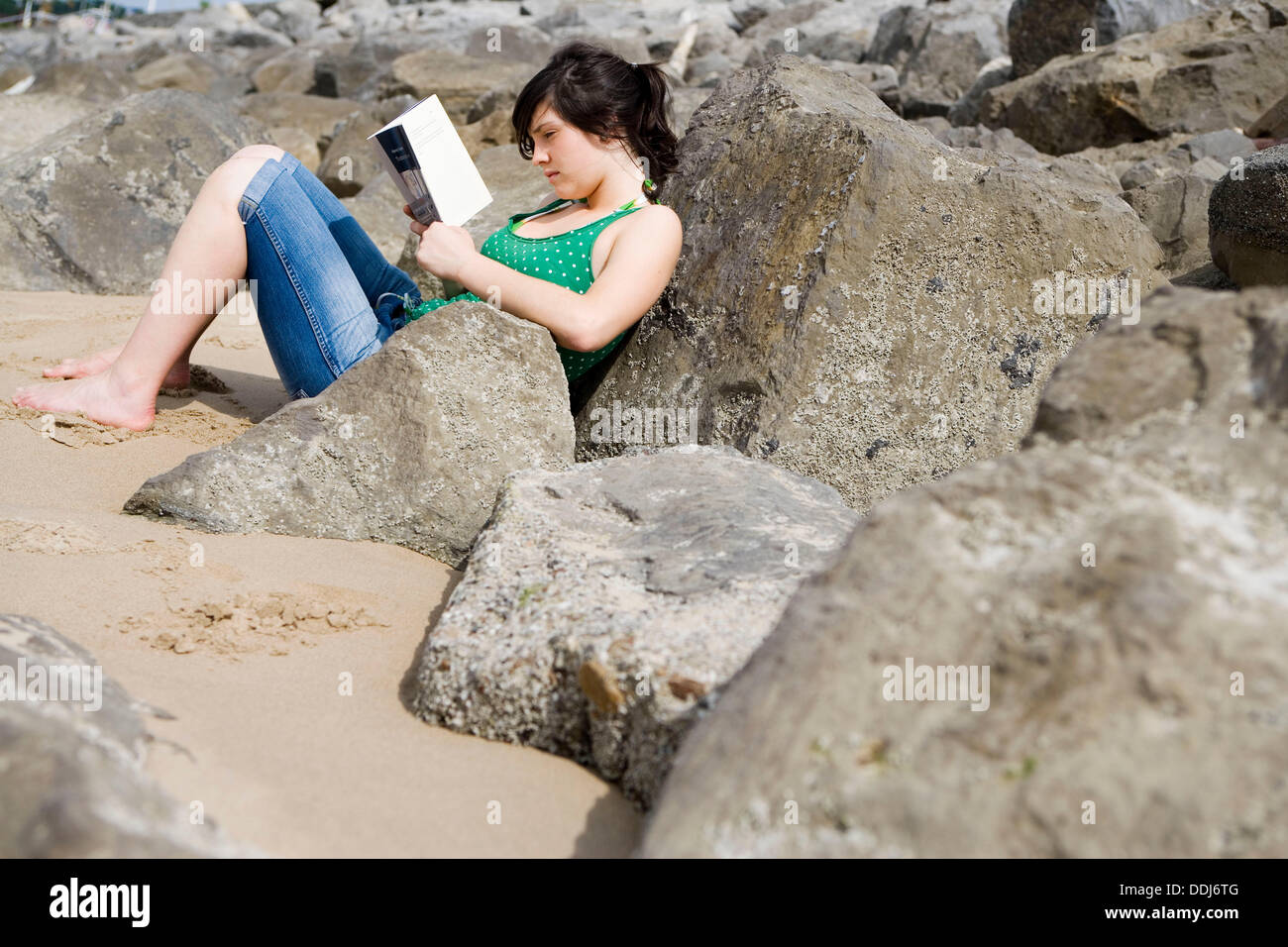 Seventeen year old girl reading at beach. - Stock Image
