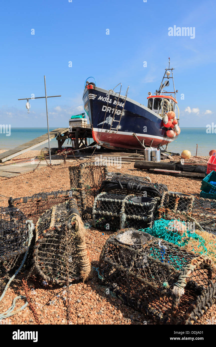 Fishing boat and lobster pots on the south coast shingle beach in Deal, Kent, England, UK, Britain - Stock Image
