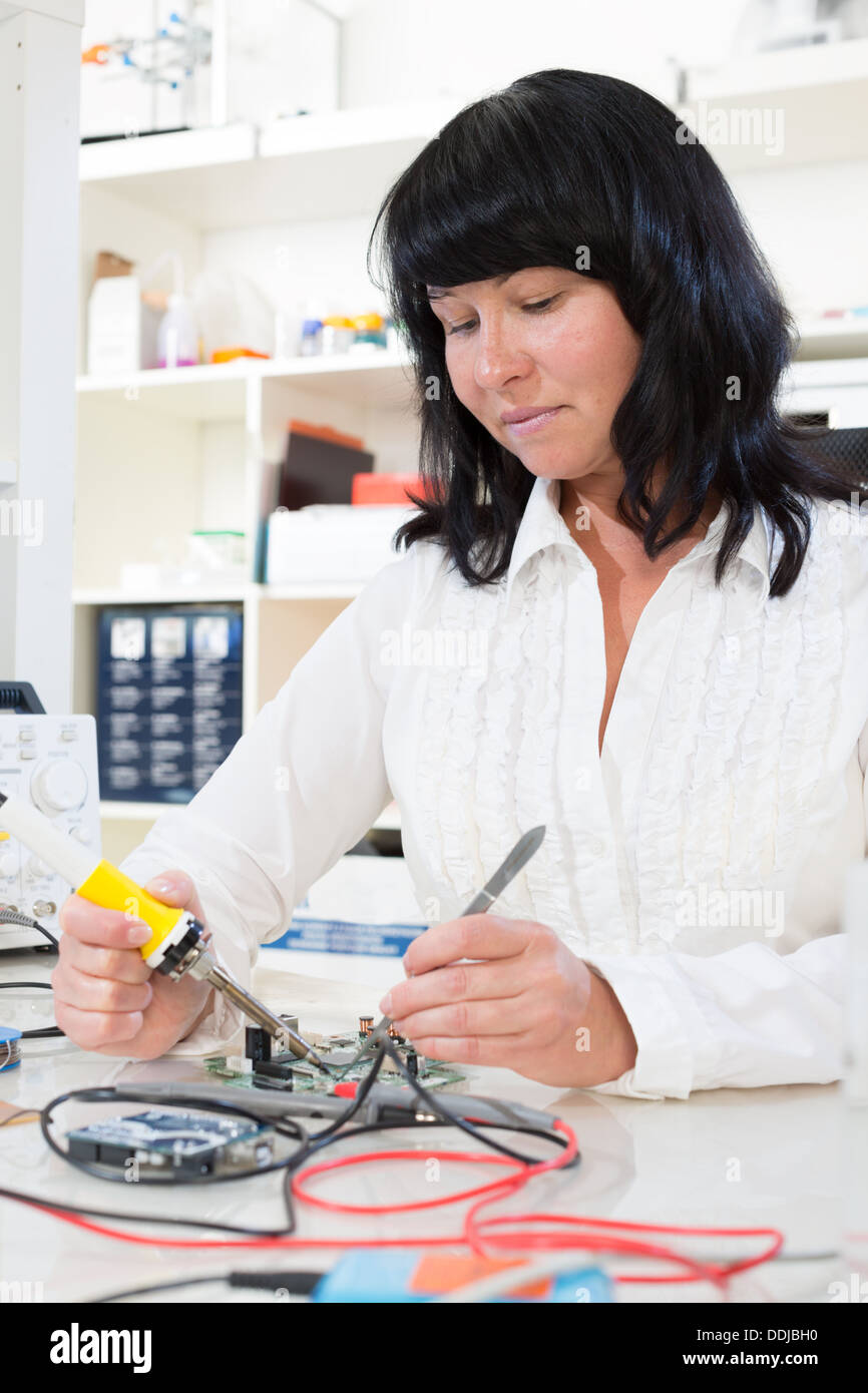 woman measures the current using a tester - Stock Image