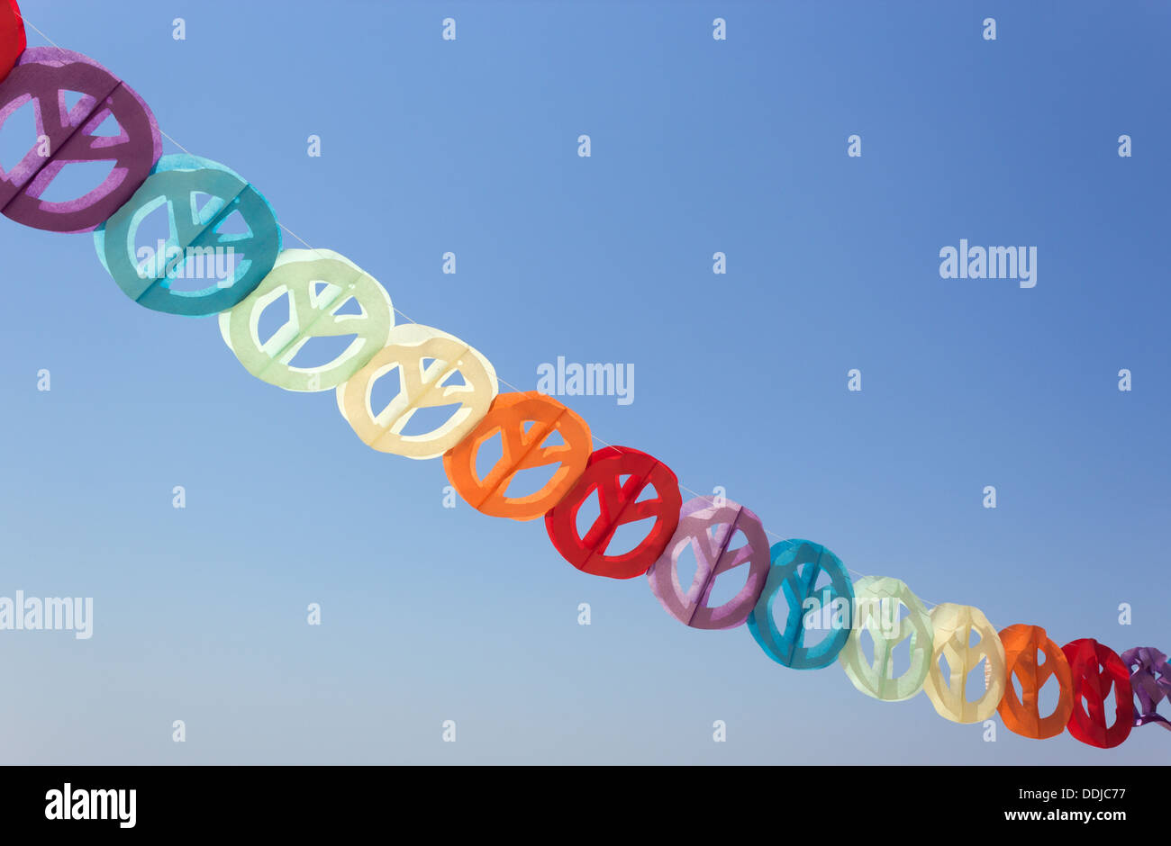 Paper garland of coloured peace signs against blue sky. - Stock Image