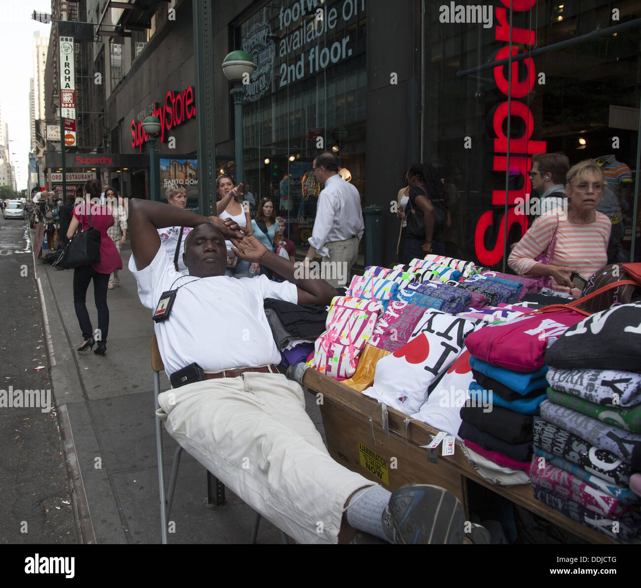 t-shirt vendor in a relaxed pose near Times Square in Manhattan, NYC. - Stock Image