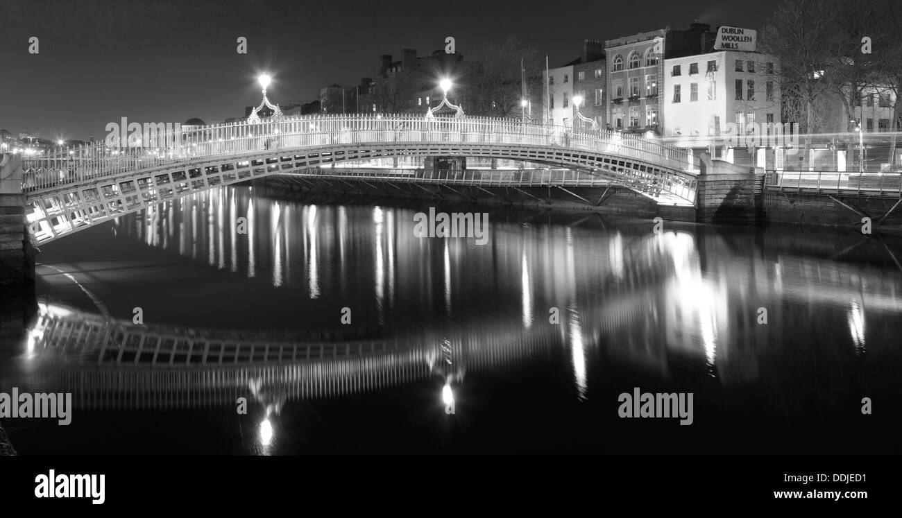 The Ha'penny bridge Dublin Ireland at night in black and white with reflections - Stock Image