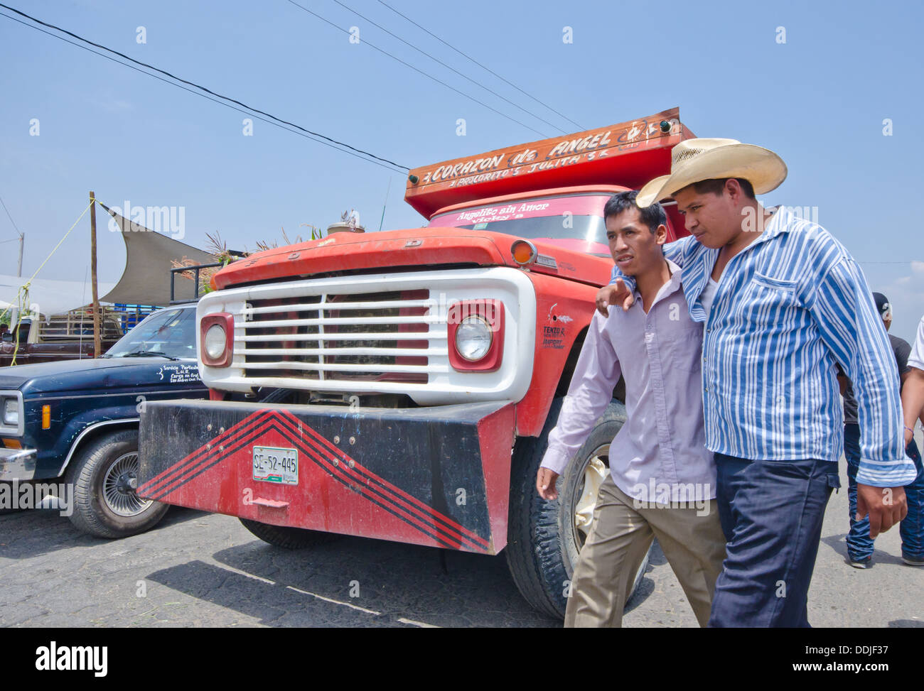 Two male friends, one with arm around the other, walking on road in front of truck in Mexico - Stock Image