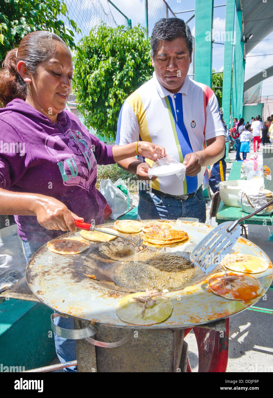 Food festival in Puebla city, Mexico. A woman prepares chalupas for customers. A man is being served. - Stock Image