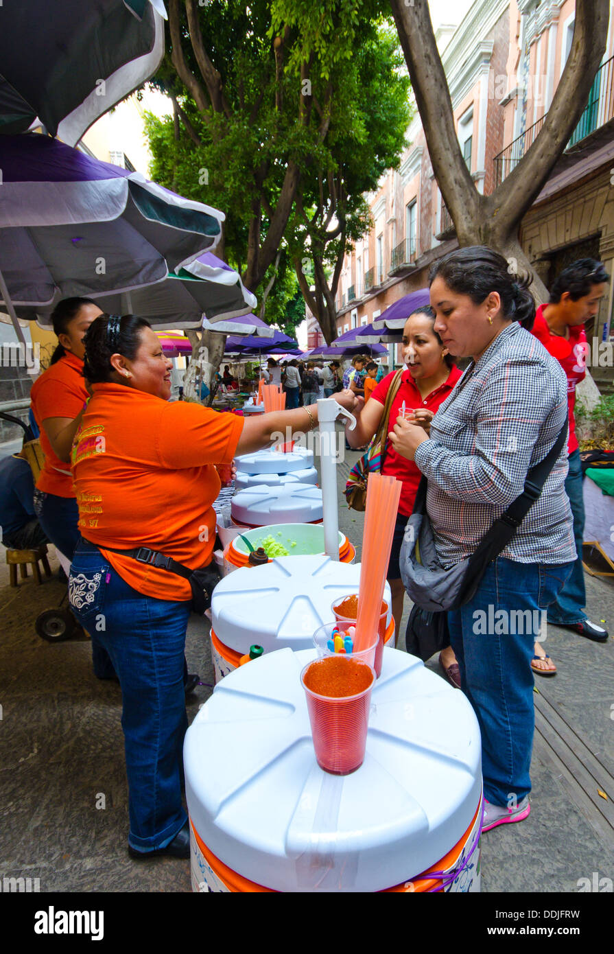 Women selling traditional thirst quenching ices and slushies in the streets of Centro Historico in Puebla, . - Stock Image
