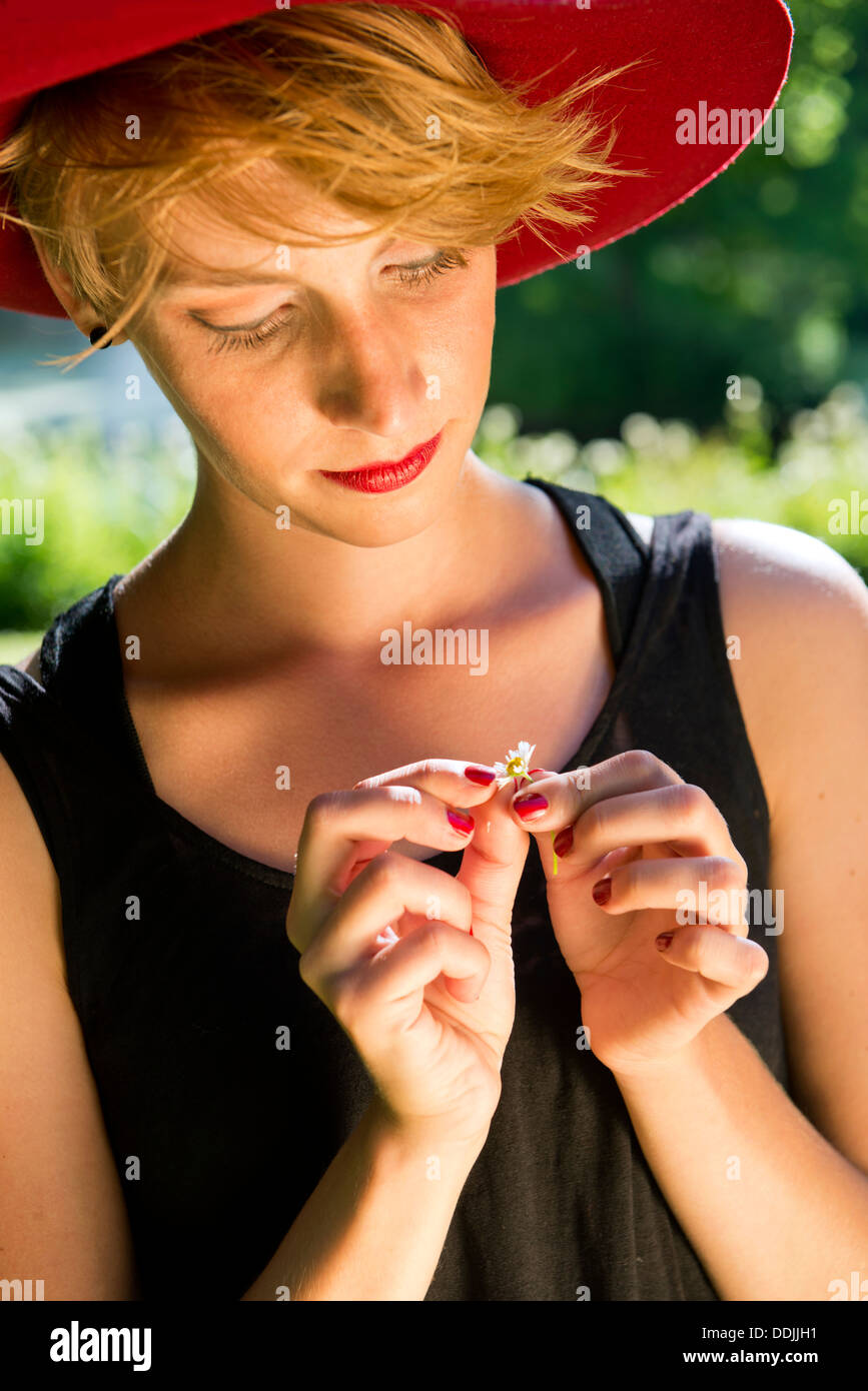 Young woman, wearing a red felt hat and a black dress, gently pulling the petals from a daisy - Stock Image