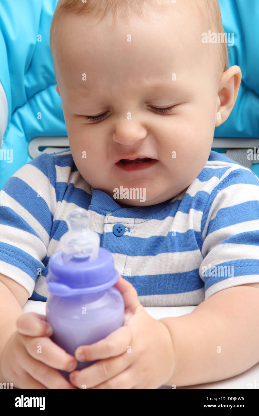 baby with milk bottle unhappy - Stock Image