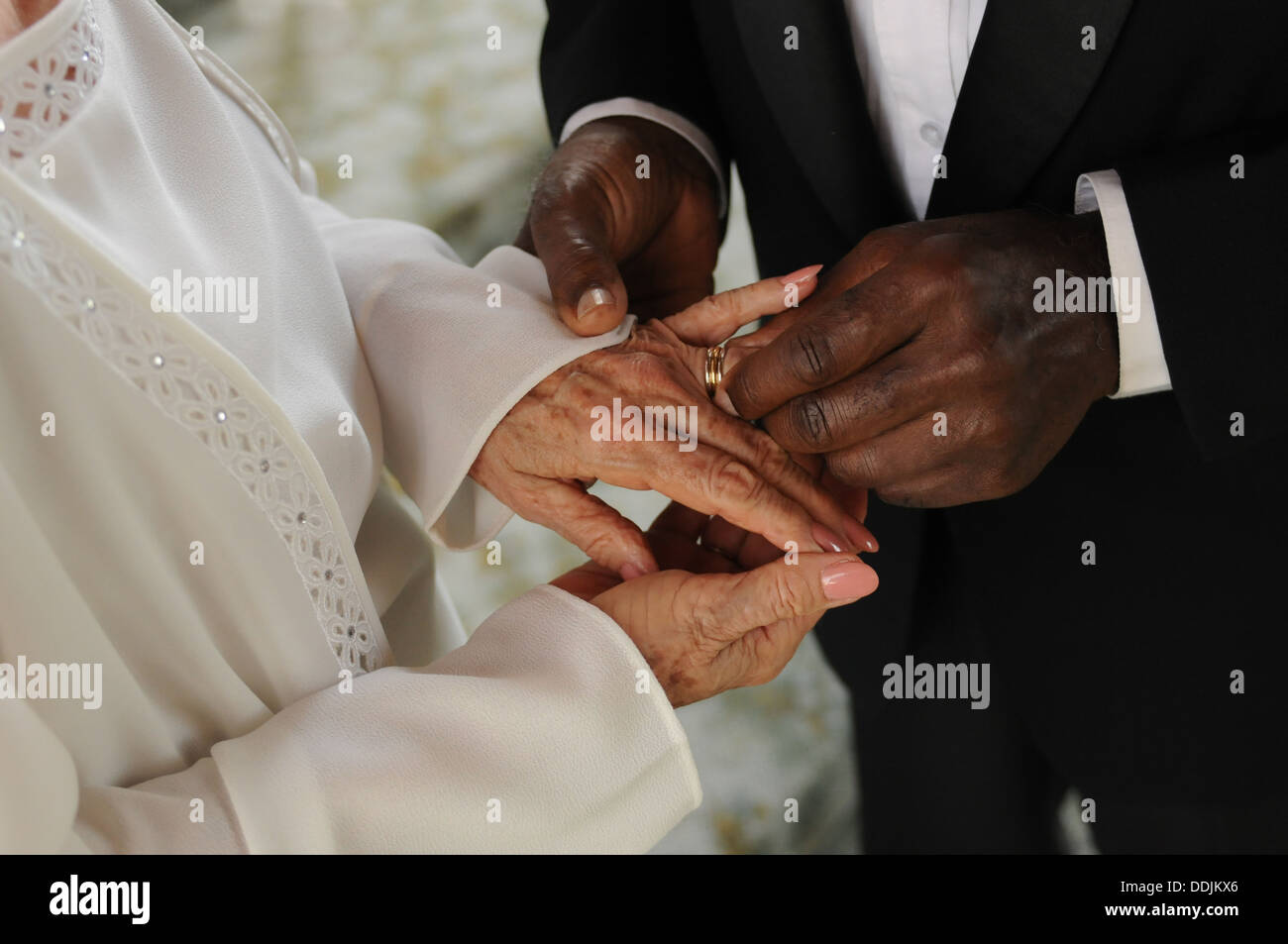 Mature multi-ethnic couple exchanging  wedding rings during the wedding ceremony - Stock Image