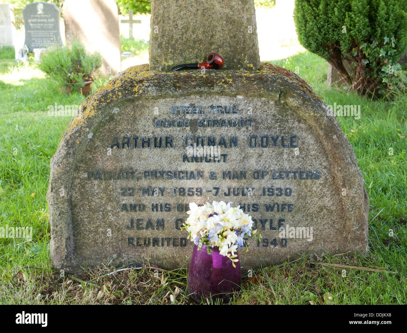 Grave of Sir Arthur Conan Doyle and his wife in the graveyard of Church of All Saints Minstead Hampshire England UK - Stock Image