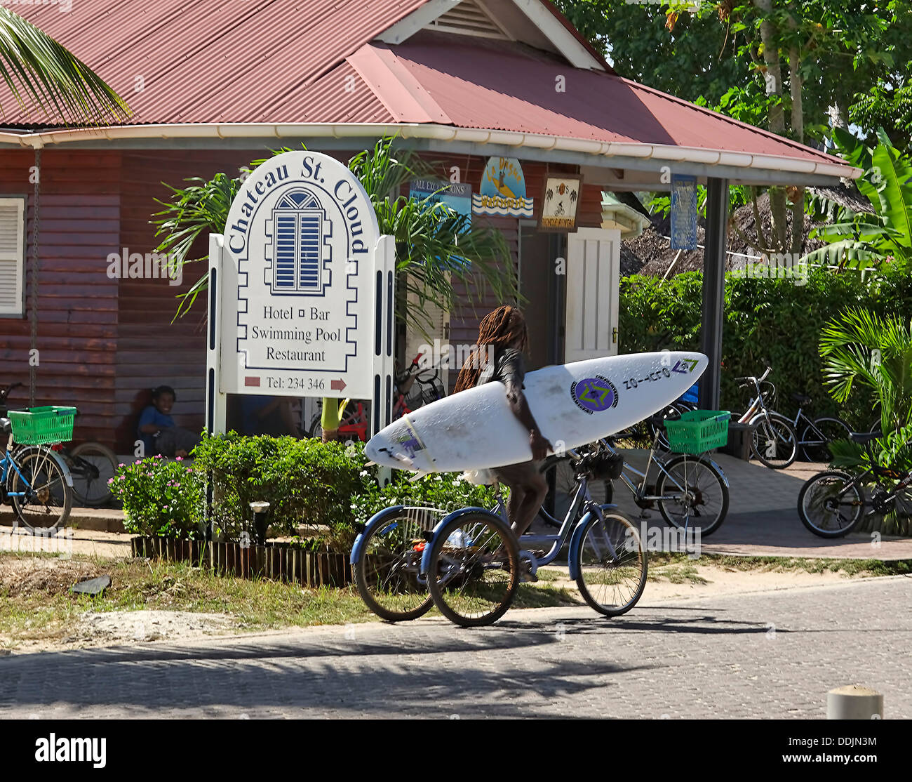 Chateu St. Claude Church, Surfer on bicycle, La Digue, Seychelles - Stock Image