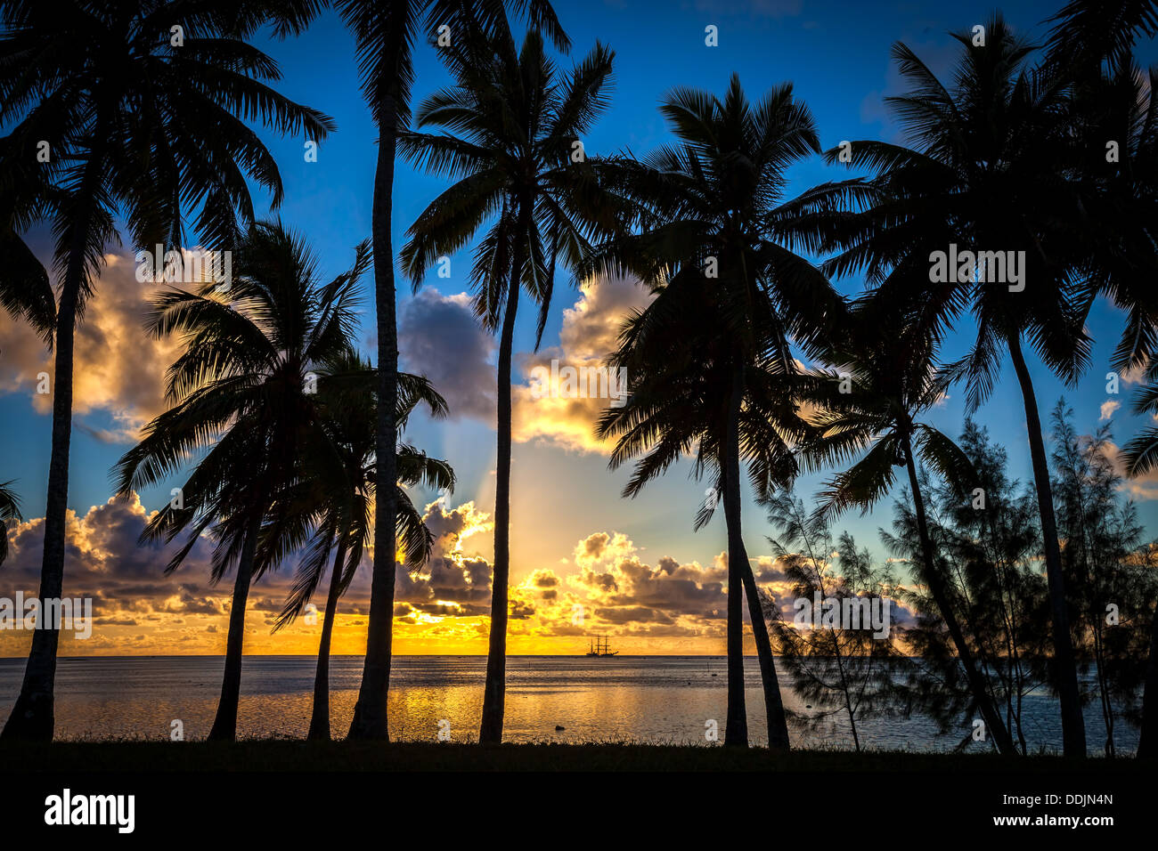 COOK ISLANDS, Aitutaki Island, tropical sunset colors in Amuri beach with a silhouette of palm trees framing a Tall Ship - Stock Image