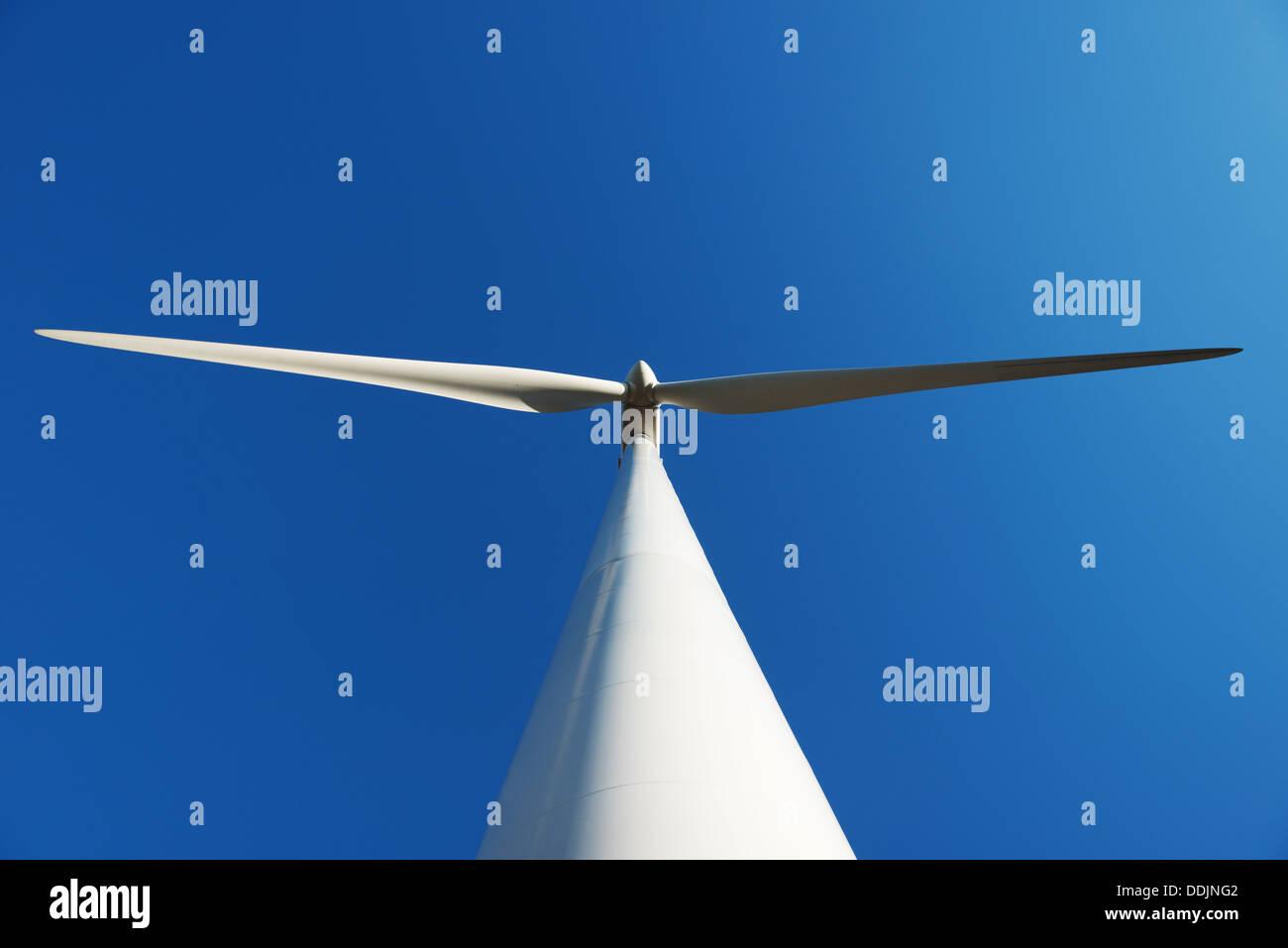 A wind turbine taken from below against blue sky - Stock Image