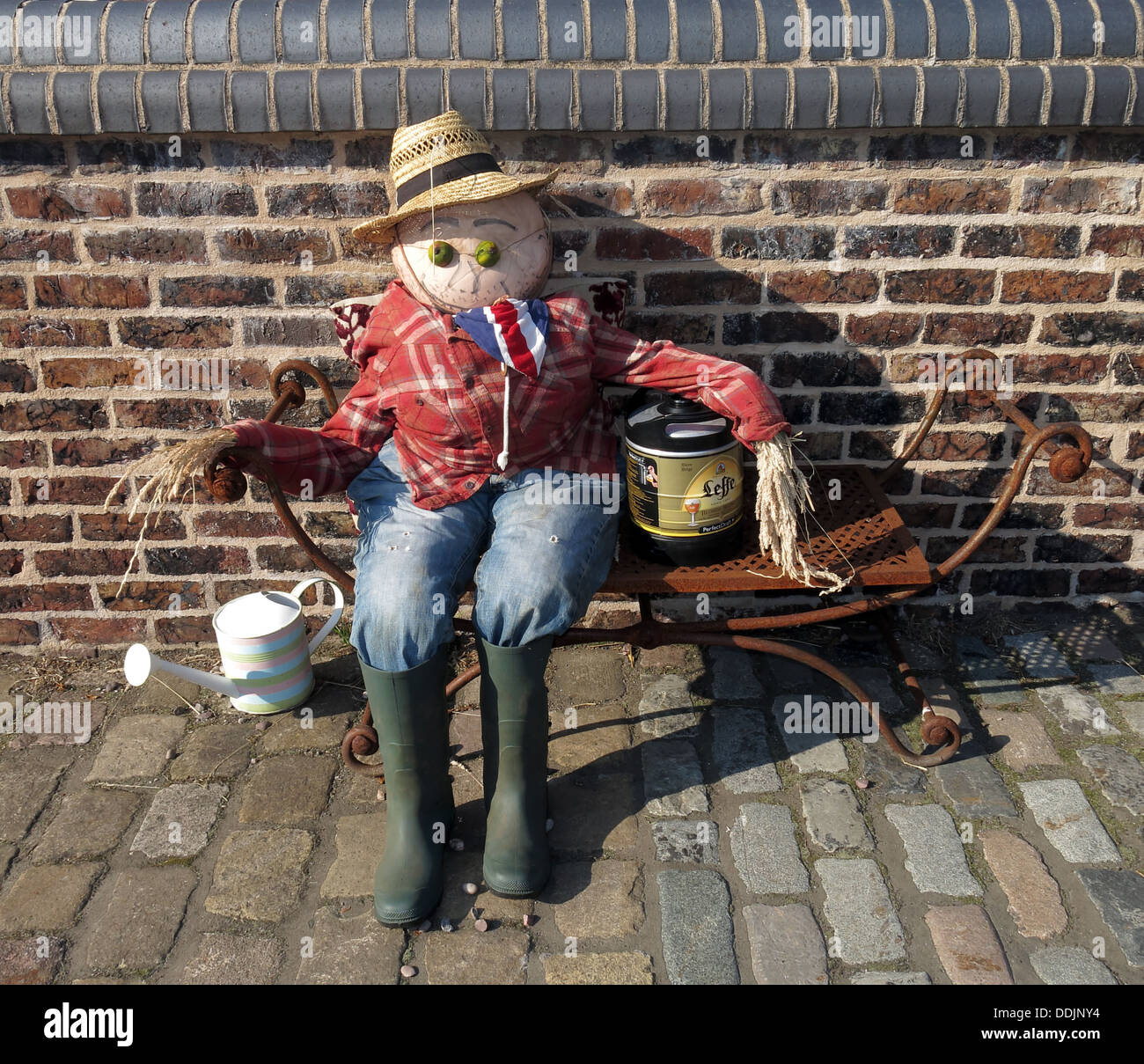 Summer Scarecrow on a bench, England, UK - Stock Image
