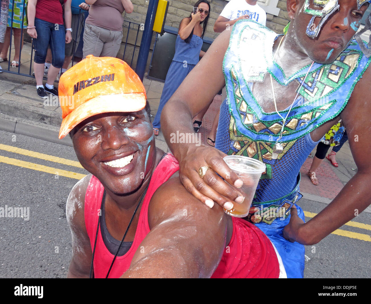 Costumed dancers with talc powder from Huddersfield Carnival 2013 African Caribbean parade street party - Stock Image