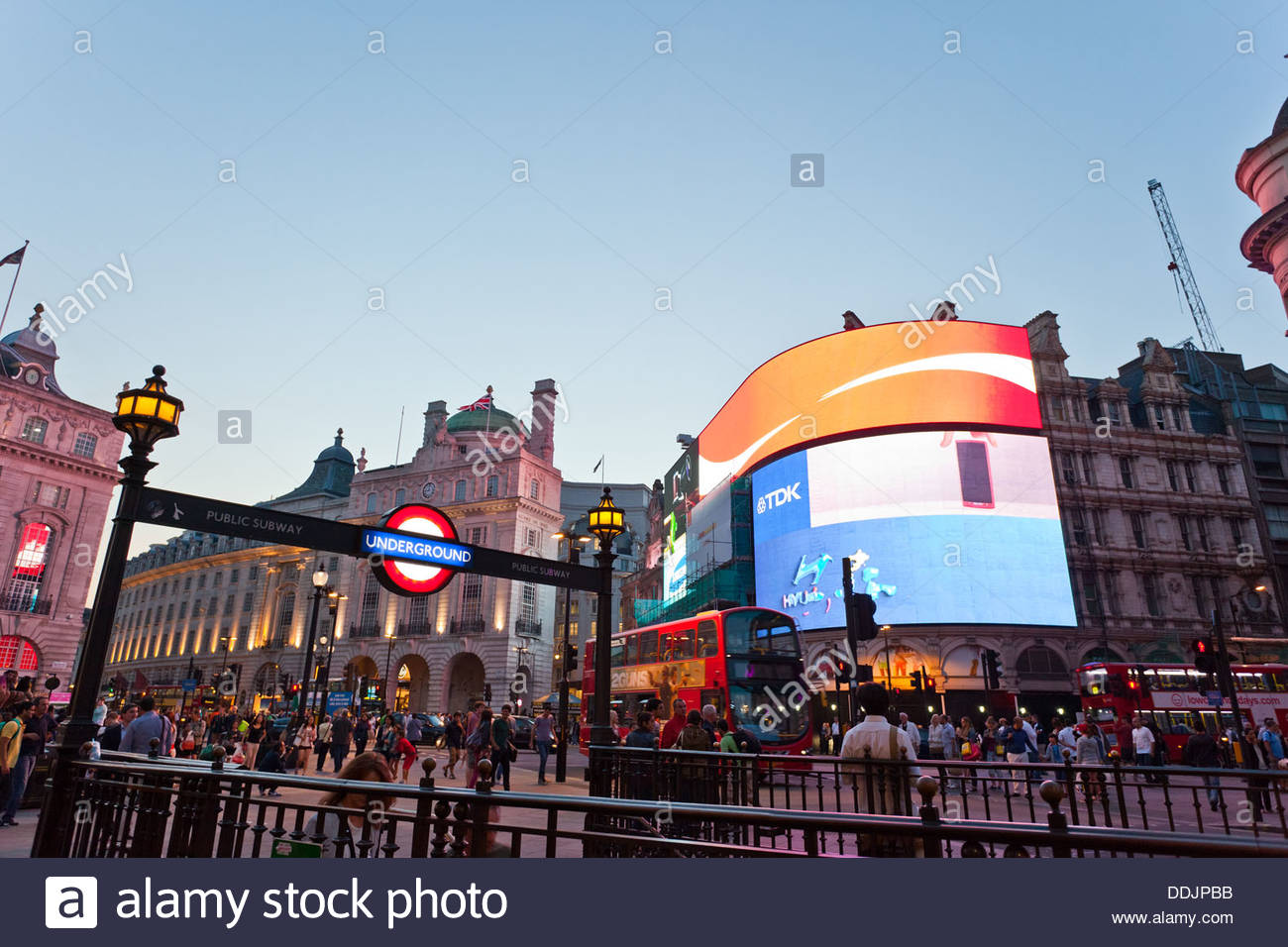 Piccadilly circus with giant tv screens, crowded of people. Underground entrance. - Stock Image