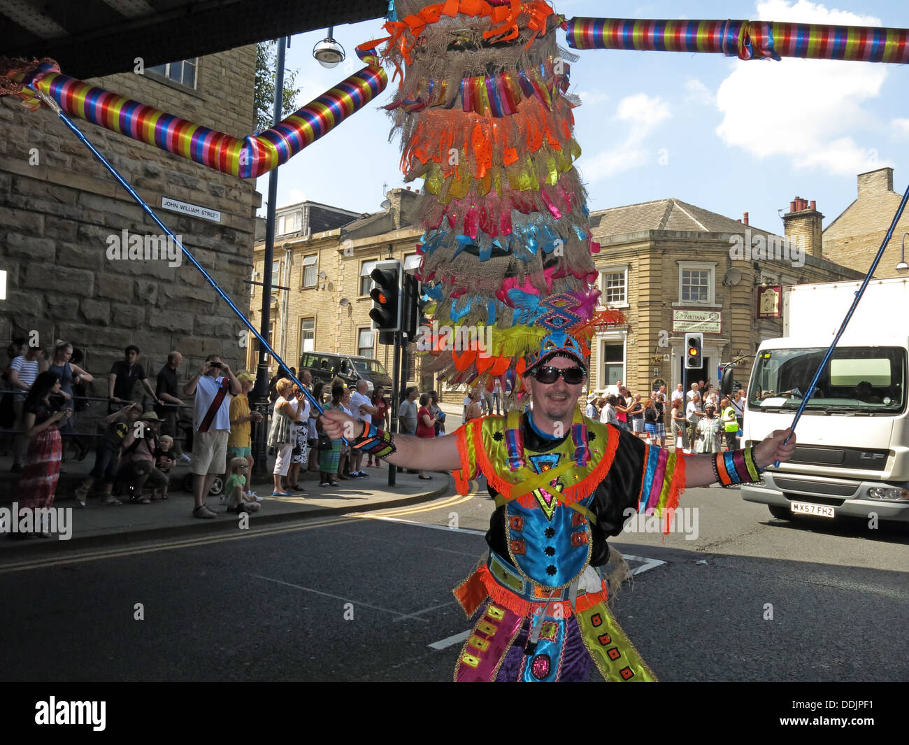 Costumed dancer under railway bridge from Huddersfield Carnival 2013 African Caribbean parade street party - Stock Image