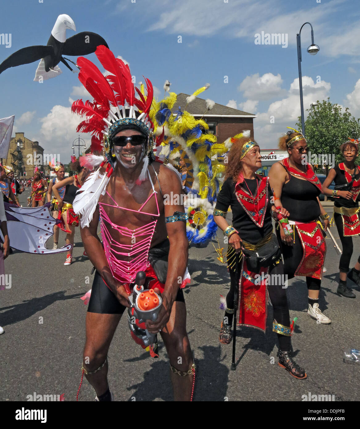 Costumed dancers in red from Huddersfield Carnival 2013 African Caribbean parade street party - Stock Image
