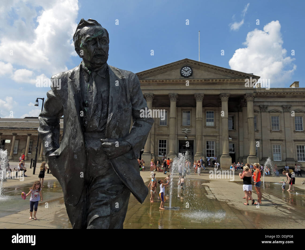 Square outside Huddersfield railway station with fountains and sculpture of Harold Wilson by Ian Walters - Stock Image