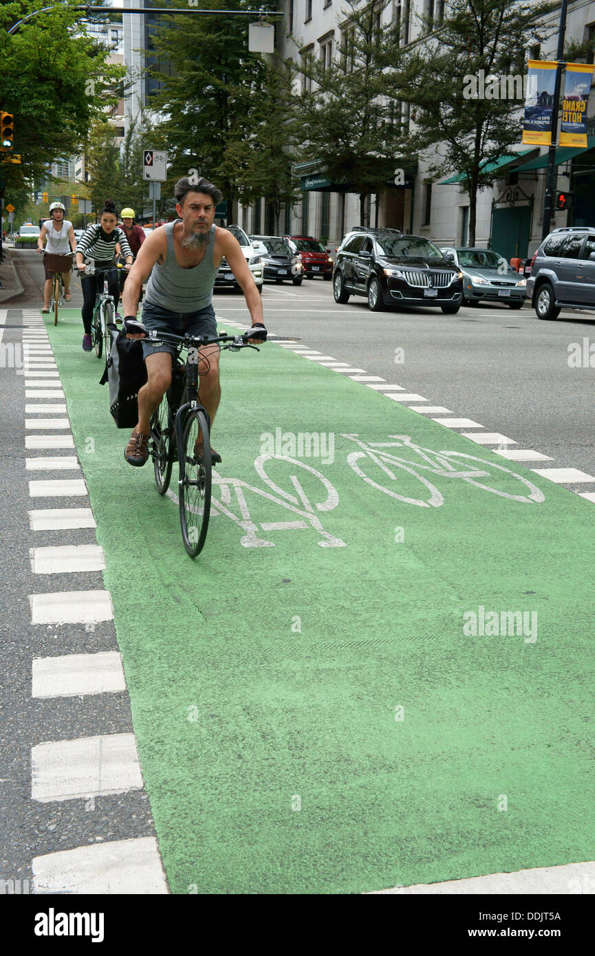 Cyclists riding along green bike lane in downtown Vancouver, BC, Canada - Stock Image