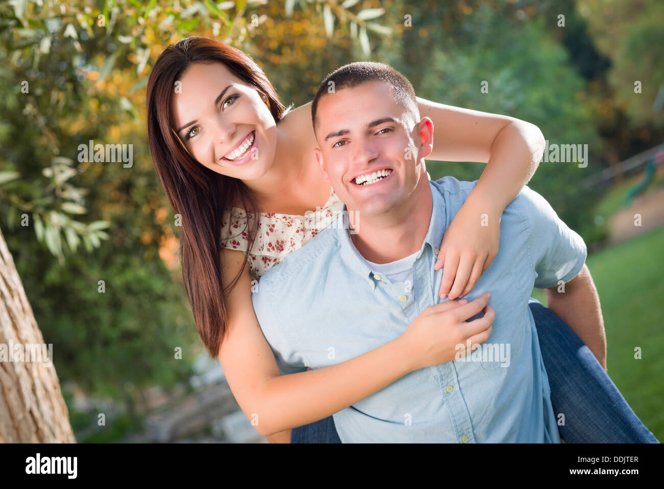 Happy Mixed Race Romantic Couple Piggyback Portrait in the Park. - Stock Image